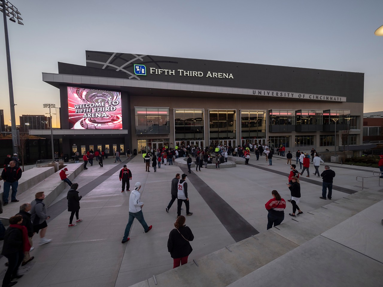 Visitors file past Fifth Third Arena's East Concourse entrance in the twilight on a game night.