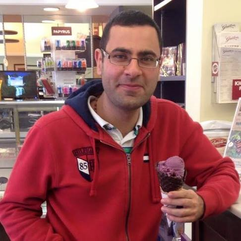 A young adult man with short dark hair and wire frame rectangular glasses, wearing  a red hooded sweatshirt, stands in an ice cream parlor holding an ice cream cone with purple ice cream on it
