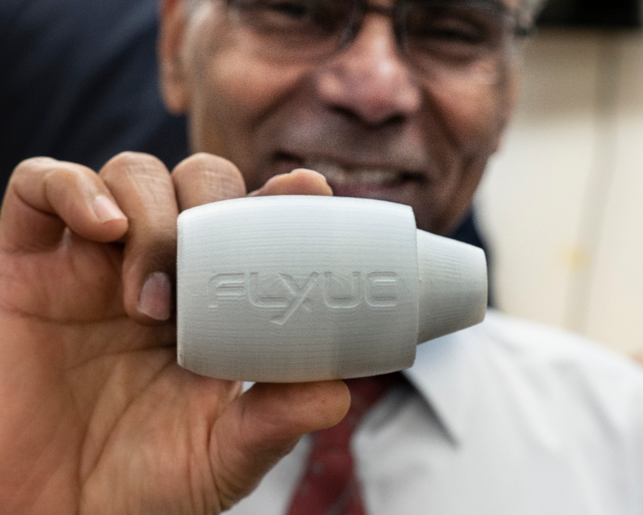 Shaaban Abdallah holds up a white 3-D printed model to his face. The model is an aircraft  fuselage featuring the logo Fly UC.
