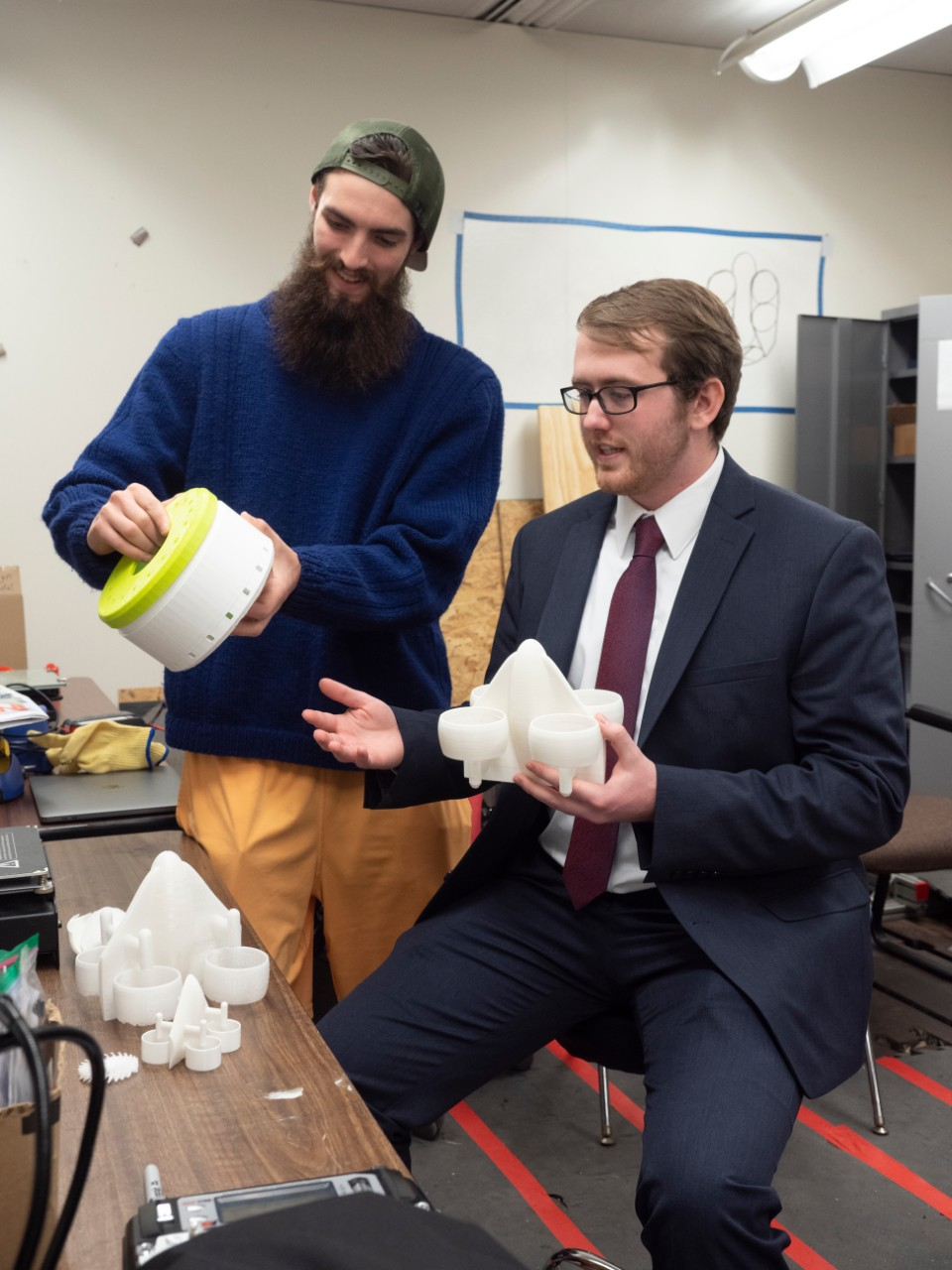 UC students hold up 3D models in their engineering lab.