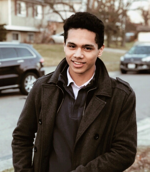 A young man with black hair stands on a sidewalk outside on a bright fall day. He is wearing a brown pea coat and brown sweater and black pants