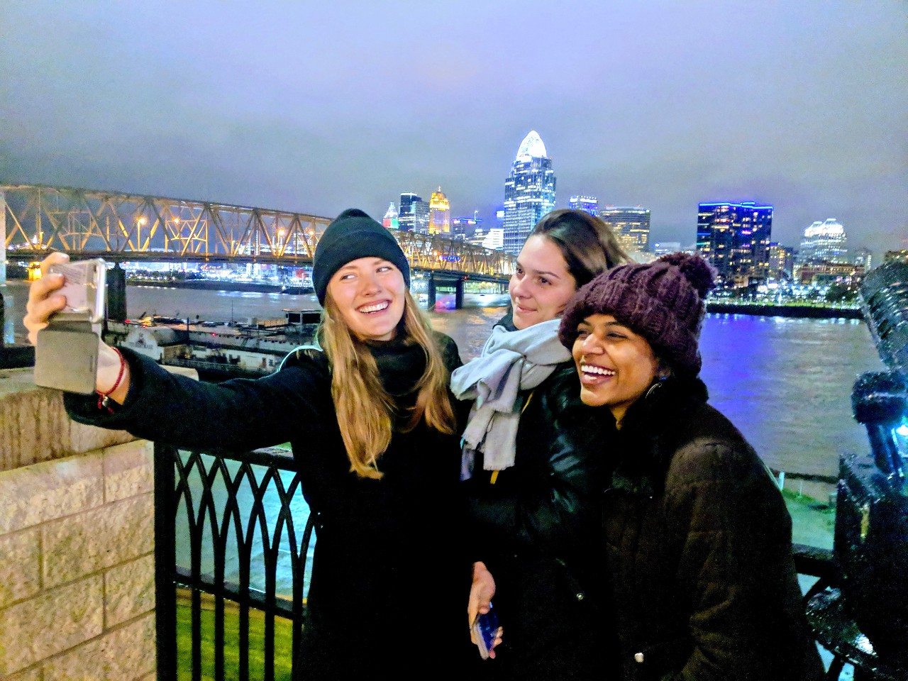 Thre women take selfies with the Cincinnati skyline in the background.