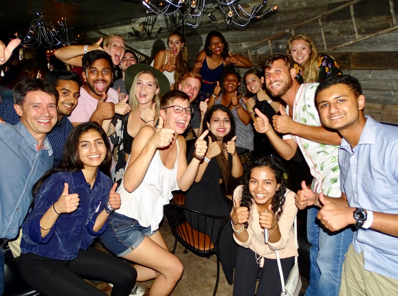 Students from UC and Montreal give the thumbs up in a Canadian cafe.