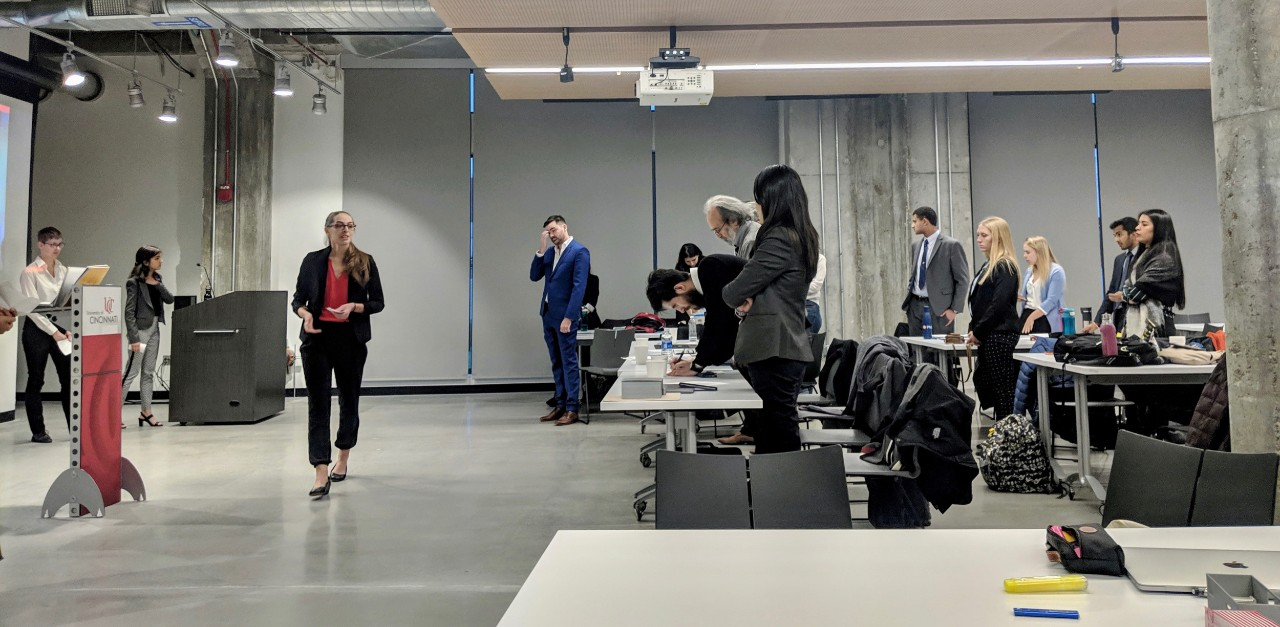Students and faculty stand at podiums and desks inside UC's 1819 Innovation Hub.
