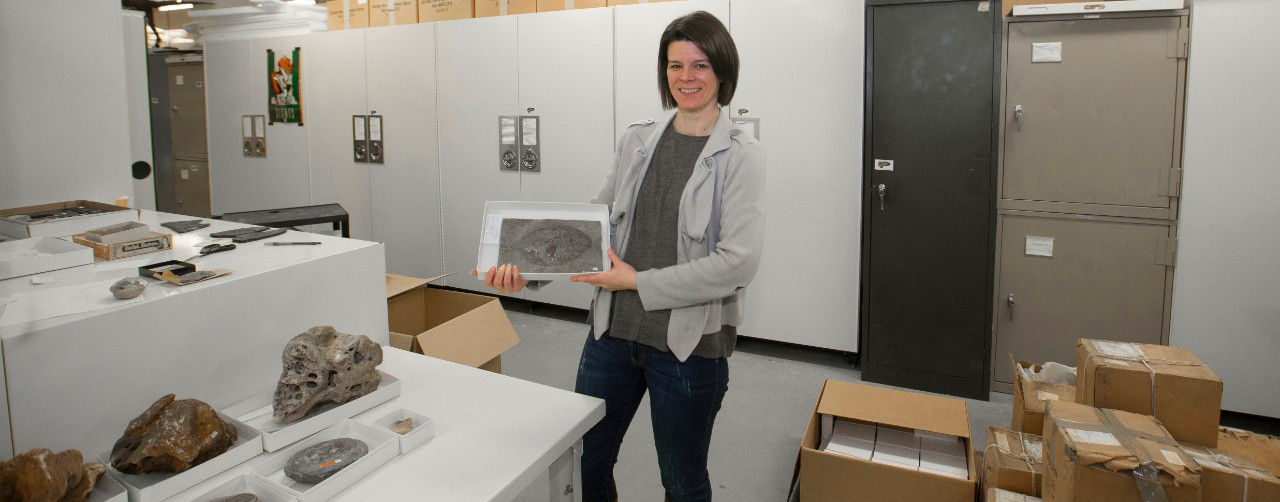 UC adjunct professor Brenda Hunda holds a fossil fish from the University of Minnesota's collection. Next to her are unopened boxes and a counter with several other fossils.