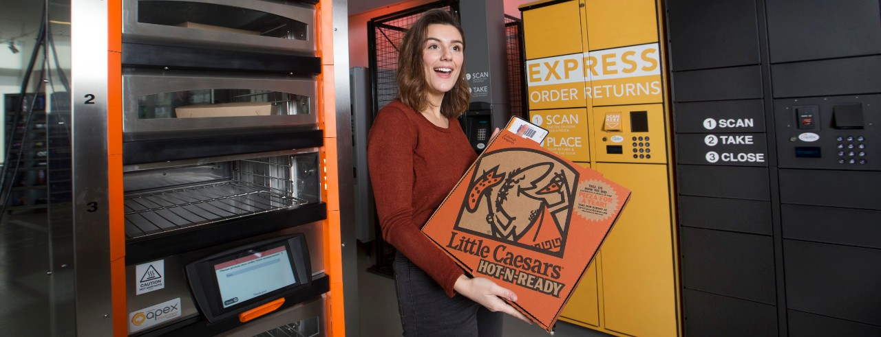 woman holding a Little Caesars Pizza box in front of a pizza warmer with keypad for PIN entry