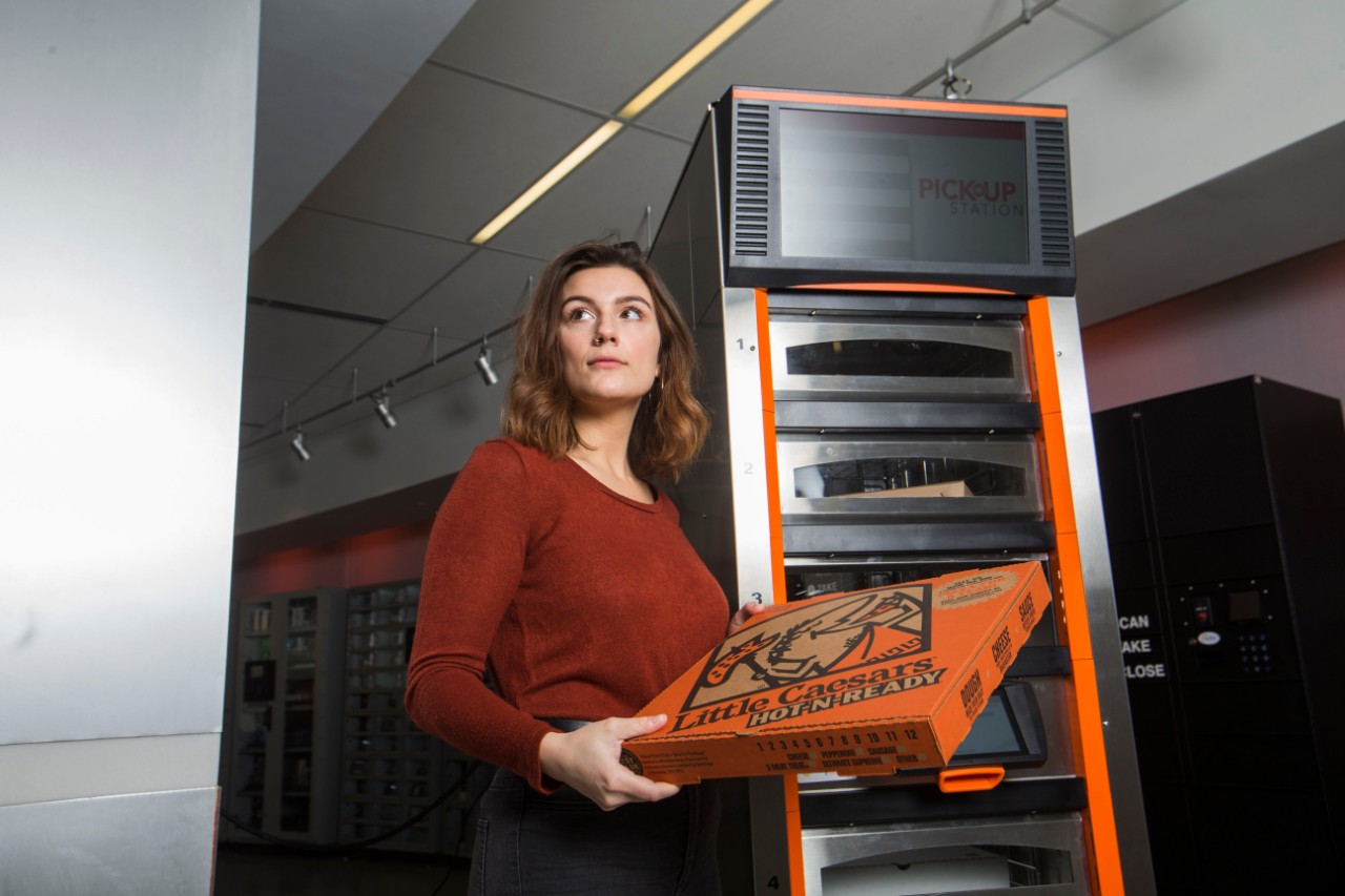 Woman holding pizza box stands in front of pizza warmer