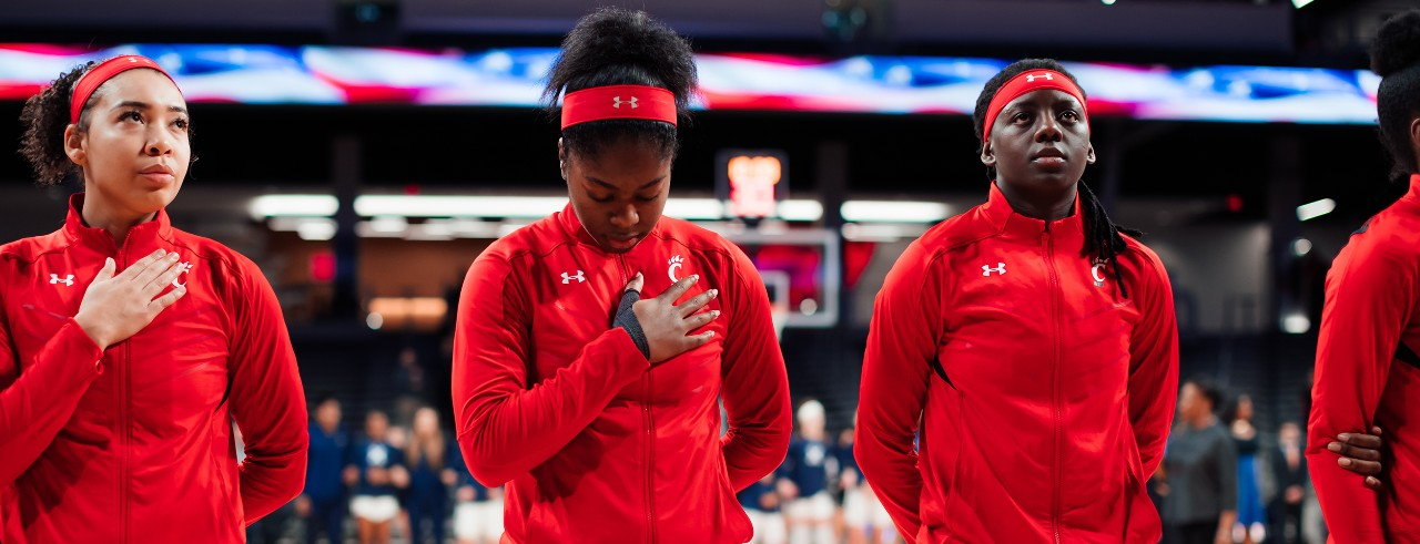 The UC women's basketball team looks on during the Anthem before a game.
