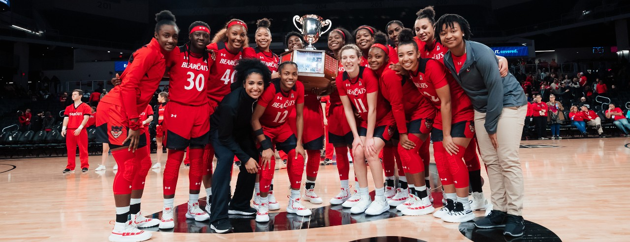 UC women's basketball team on court at Fifth Third Arena with trophy after winning Crosstown Shootout.