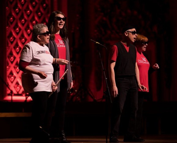 A group of singers on stage wearhing sunglasses.