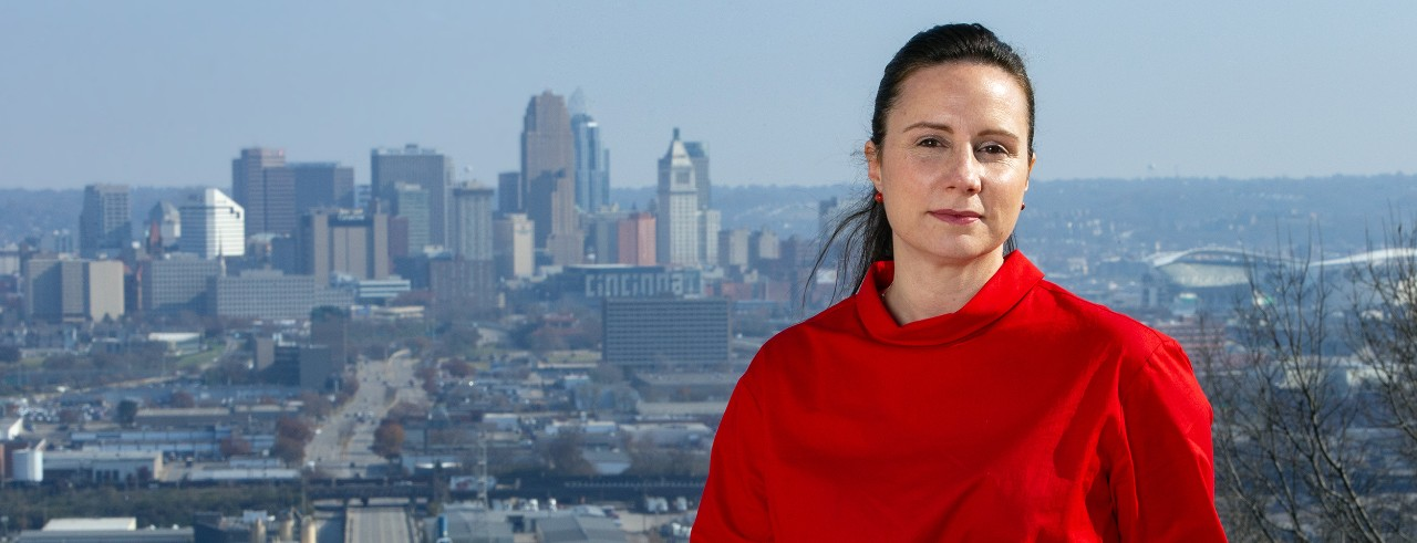 Woman in red shirt poses in front of Cincinnati skyline
