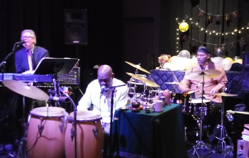 Three musicians perform on stage with drums, keyboards and bongos visible.