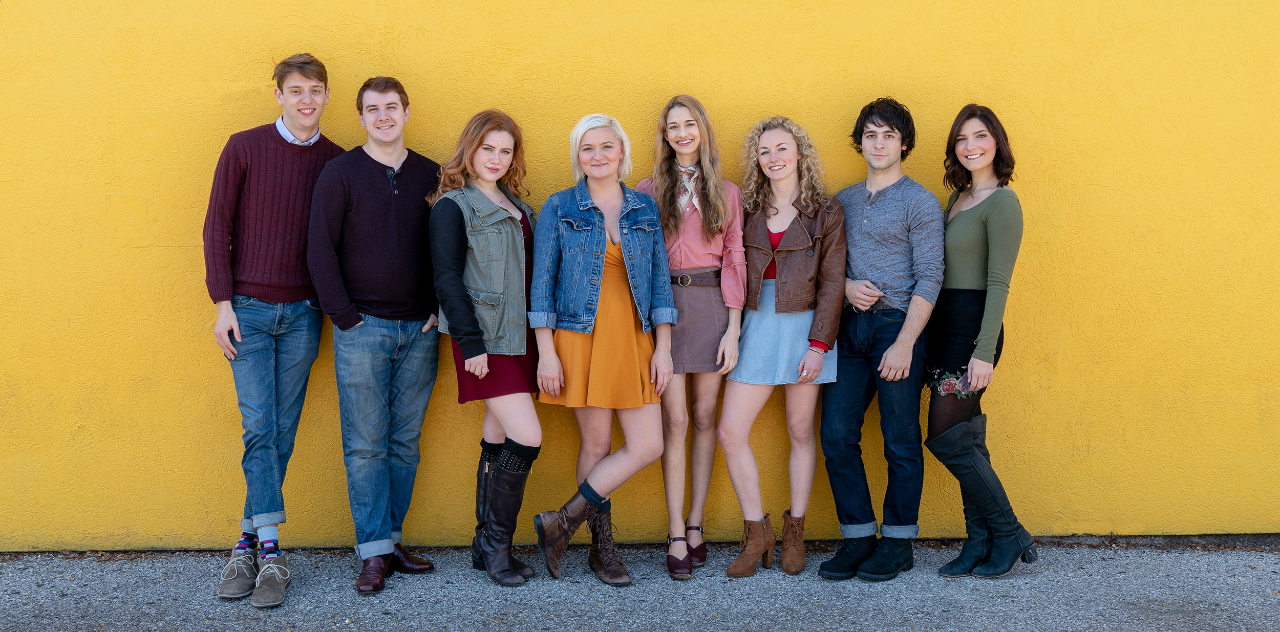 Graduating seniors or CCM Acting's Class of 2019 lined up against a yellow wall