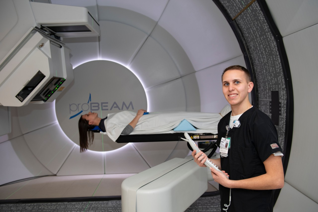 Andrew Porter stands in front of the radiation machine at the Proton Therapy Center with a patient in the background