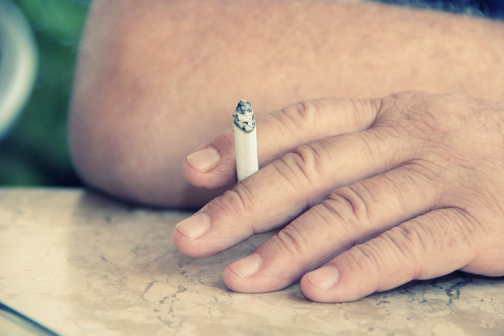 Close up of a hand holding a lit cigarette.