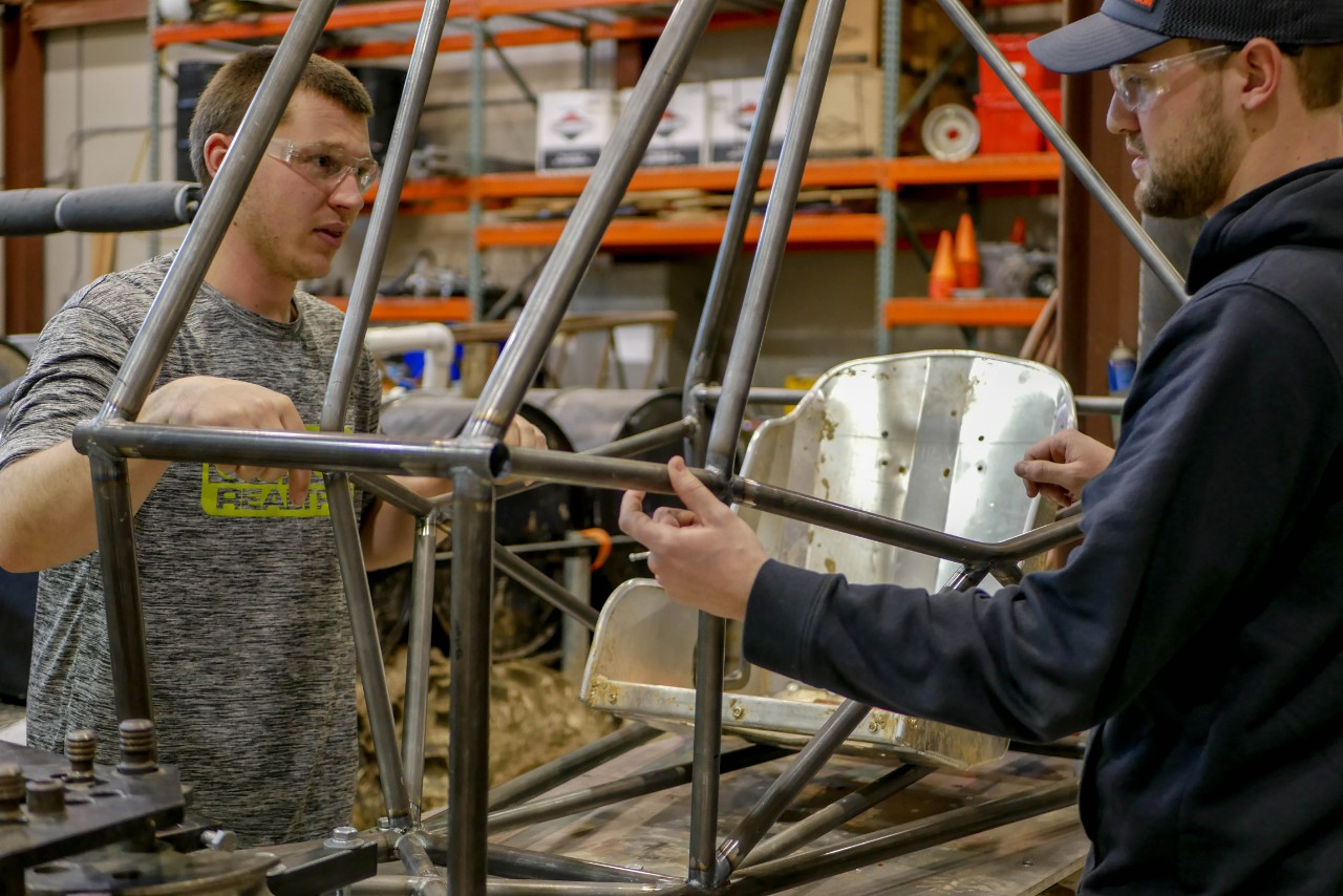 students work on frame of new car