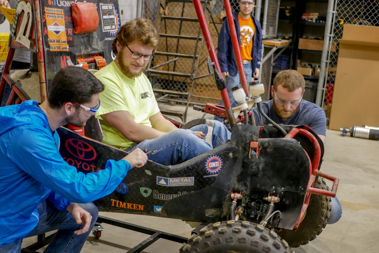 3 students work on previous year's car