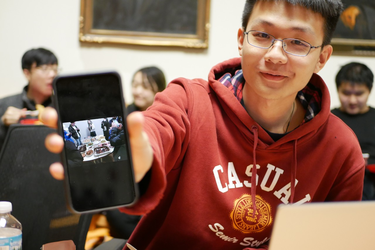 a student shows a photo of a Lunar New Year celebration on his phone