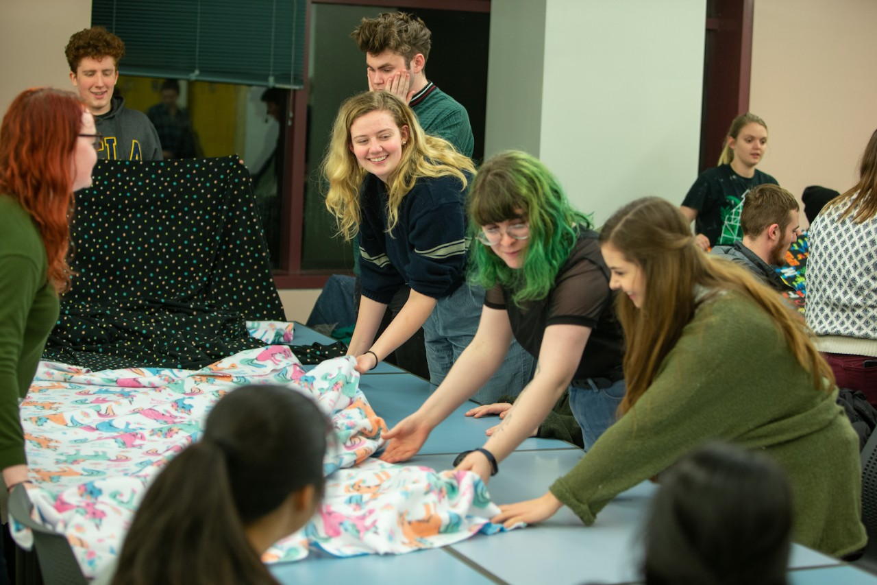A group of student gather around fabric on a large table