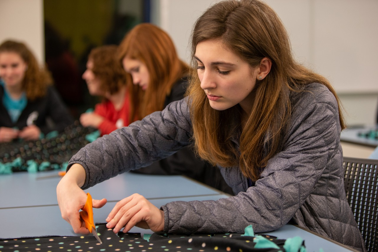 Student cuts fleece for blanket while other work in the background