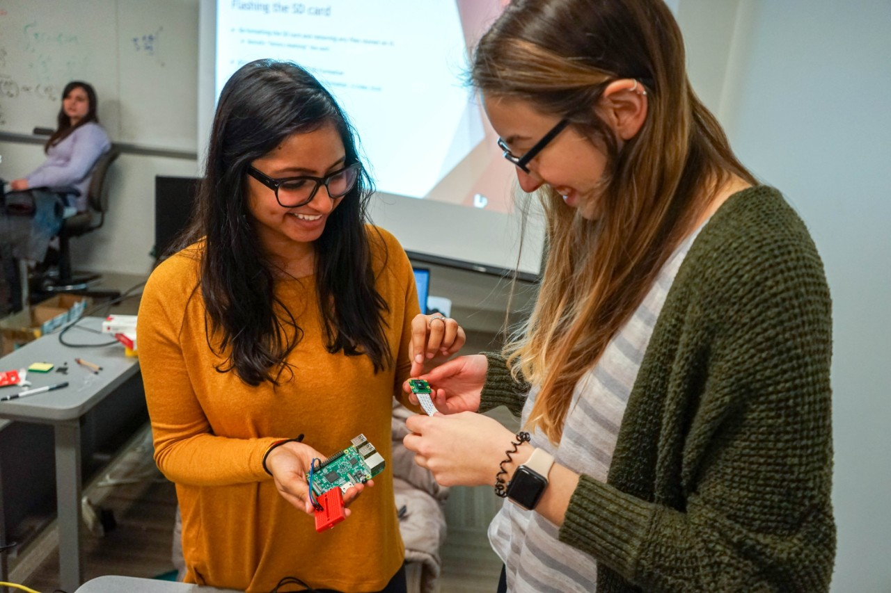 two students work on a Raspberry Pi