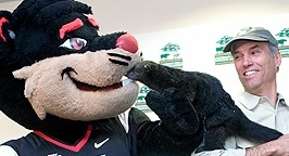mascot and animal bearcat being held by smiling man