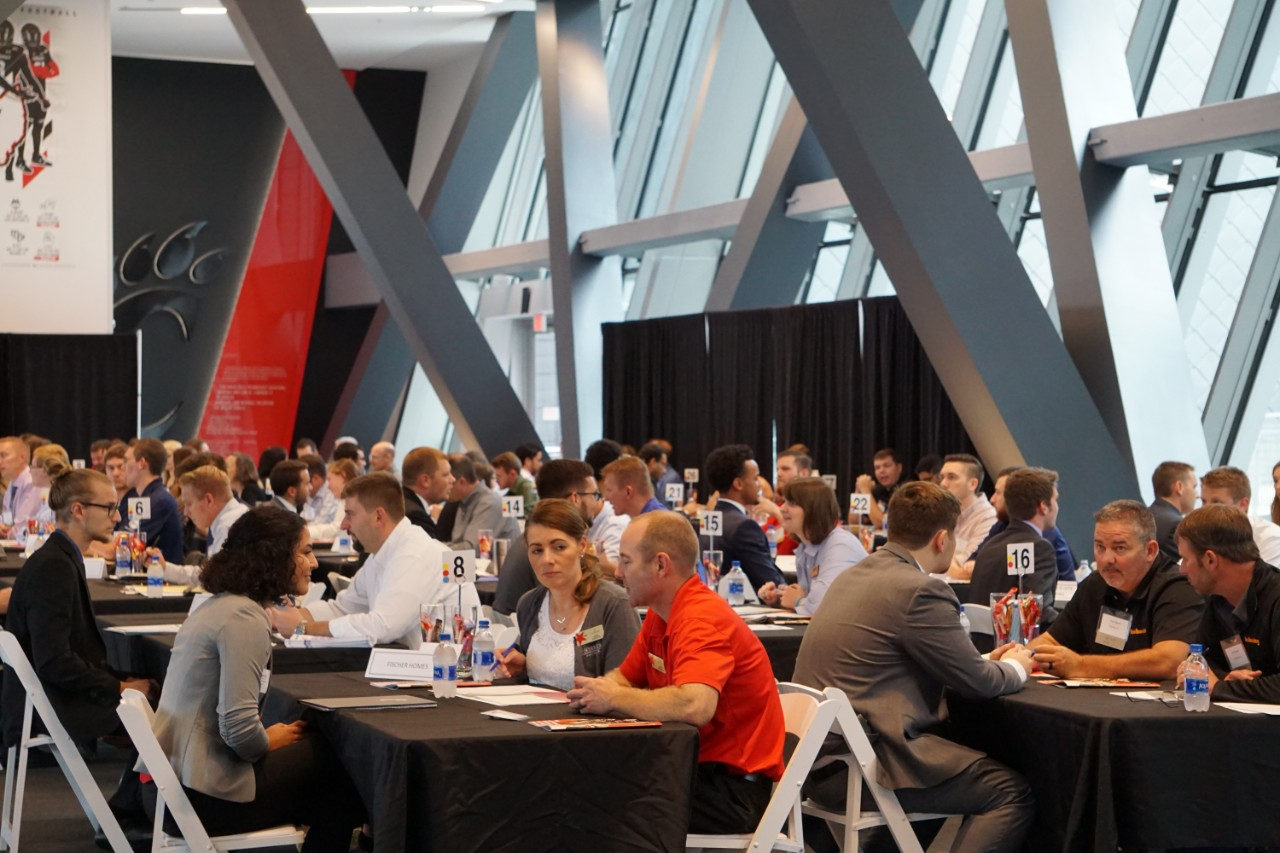 students and industry reps talk at tables