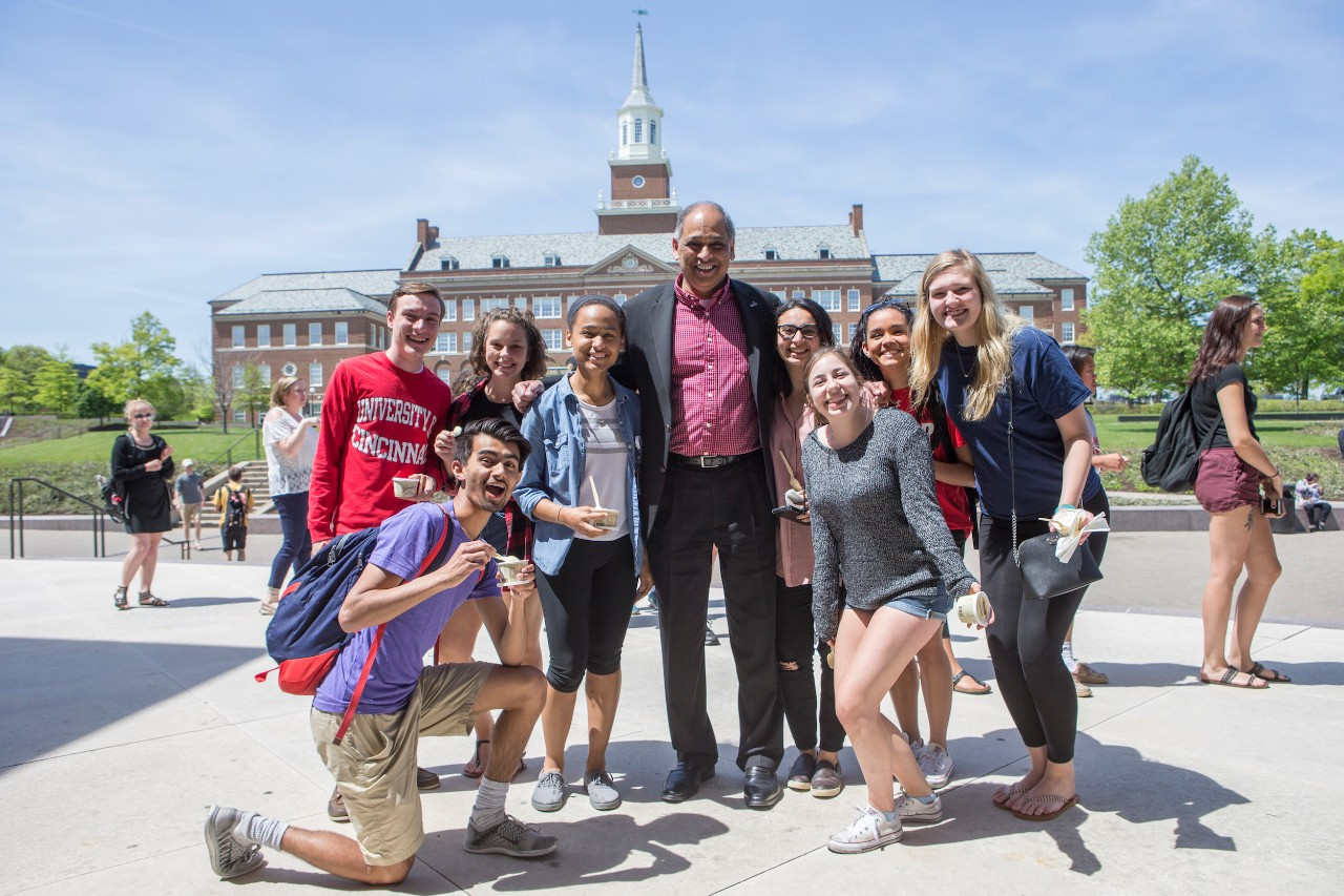 Students pose with President Neville Pinto during an ice cream social on campus.