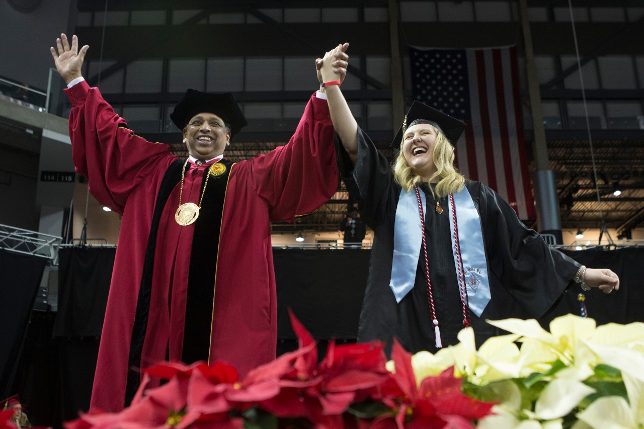 UC President Neville Pinto and a recent graduate celebrate during commencement.