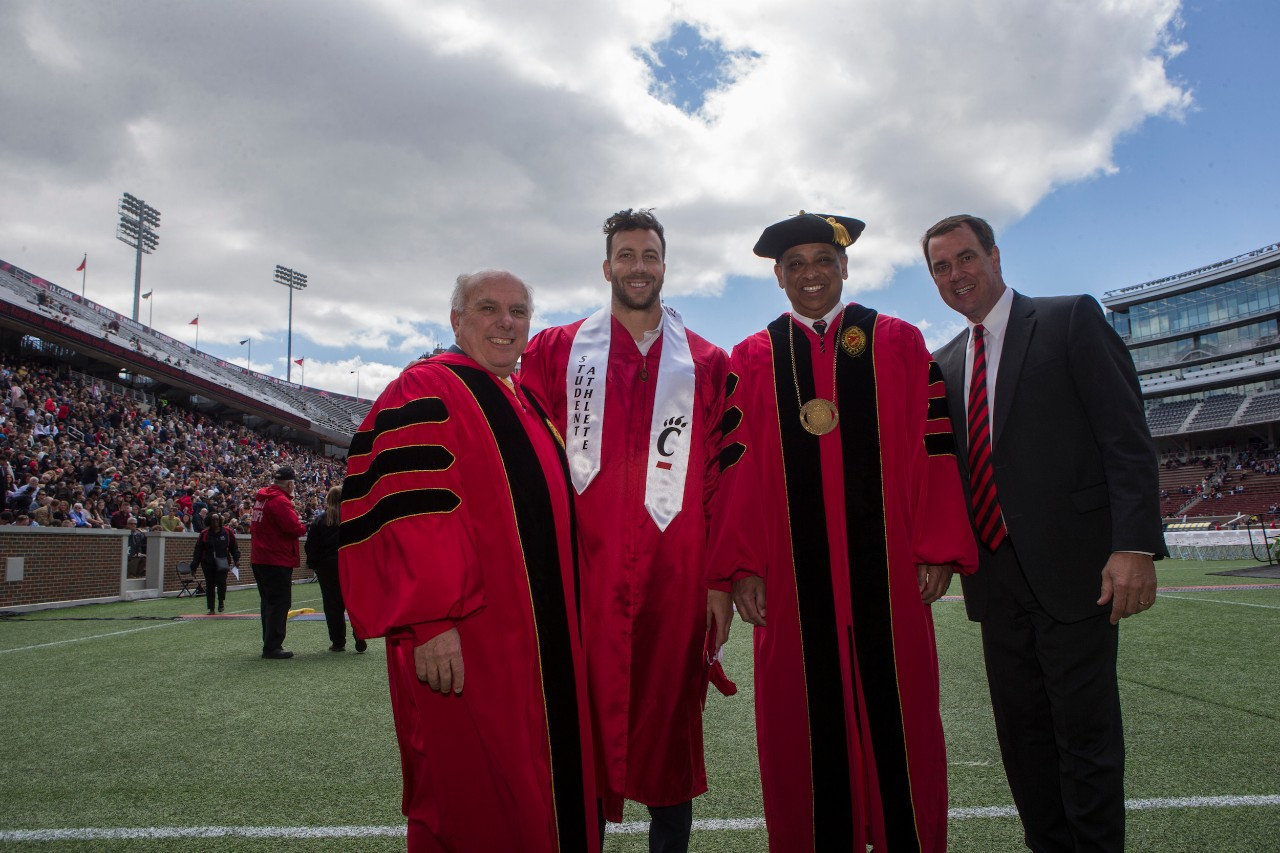 NFL linebacker  Connor Barwin stands in his graduation gown inside Nippert Stadium with President Neville Pinto, Thomas Cassady and Mike Bohn.