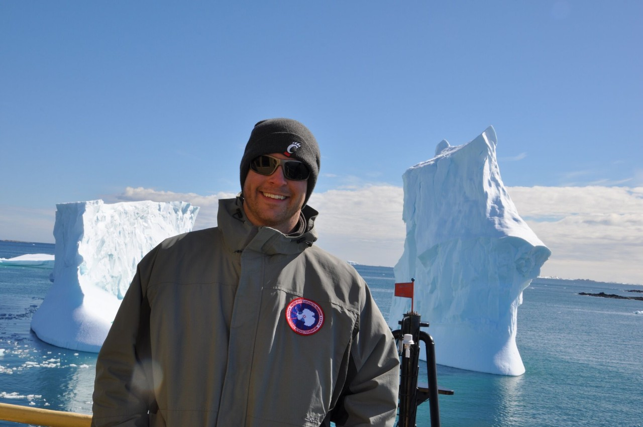 UC professor Joshua Benoit stands on a boat deck in Antarctic with icebergs behind him.