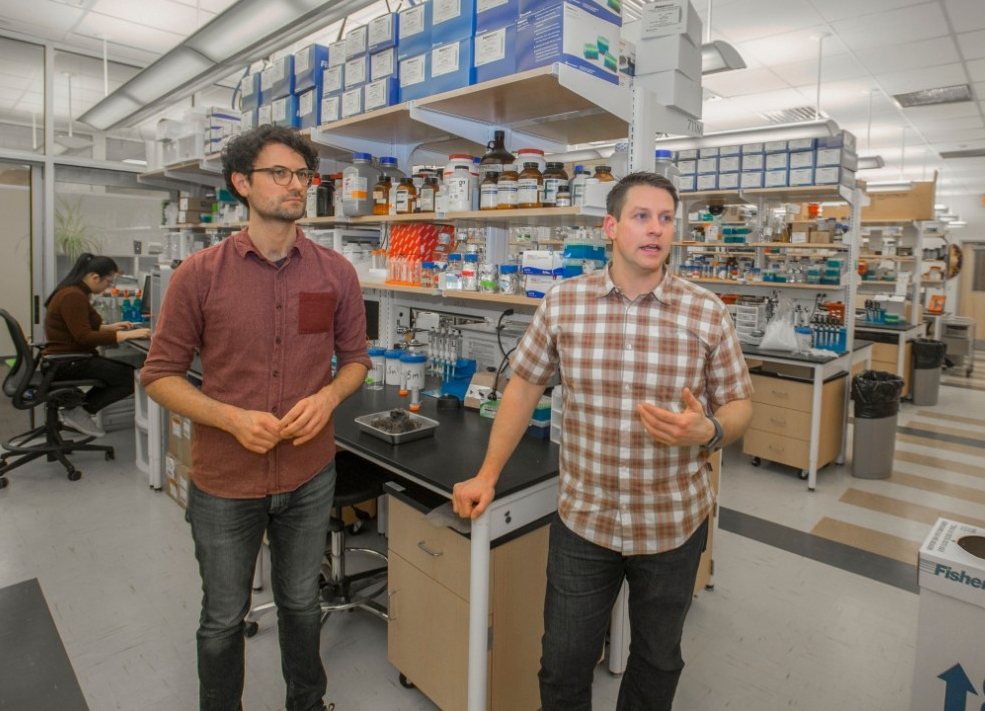 UC student Geoffrey Finch and UC professor Joshua Benoit stand in their biology lab talking about their research. Behind them are lab benches, microscopes and shelves full of lab equipment in a brightly lighted room.
