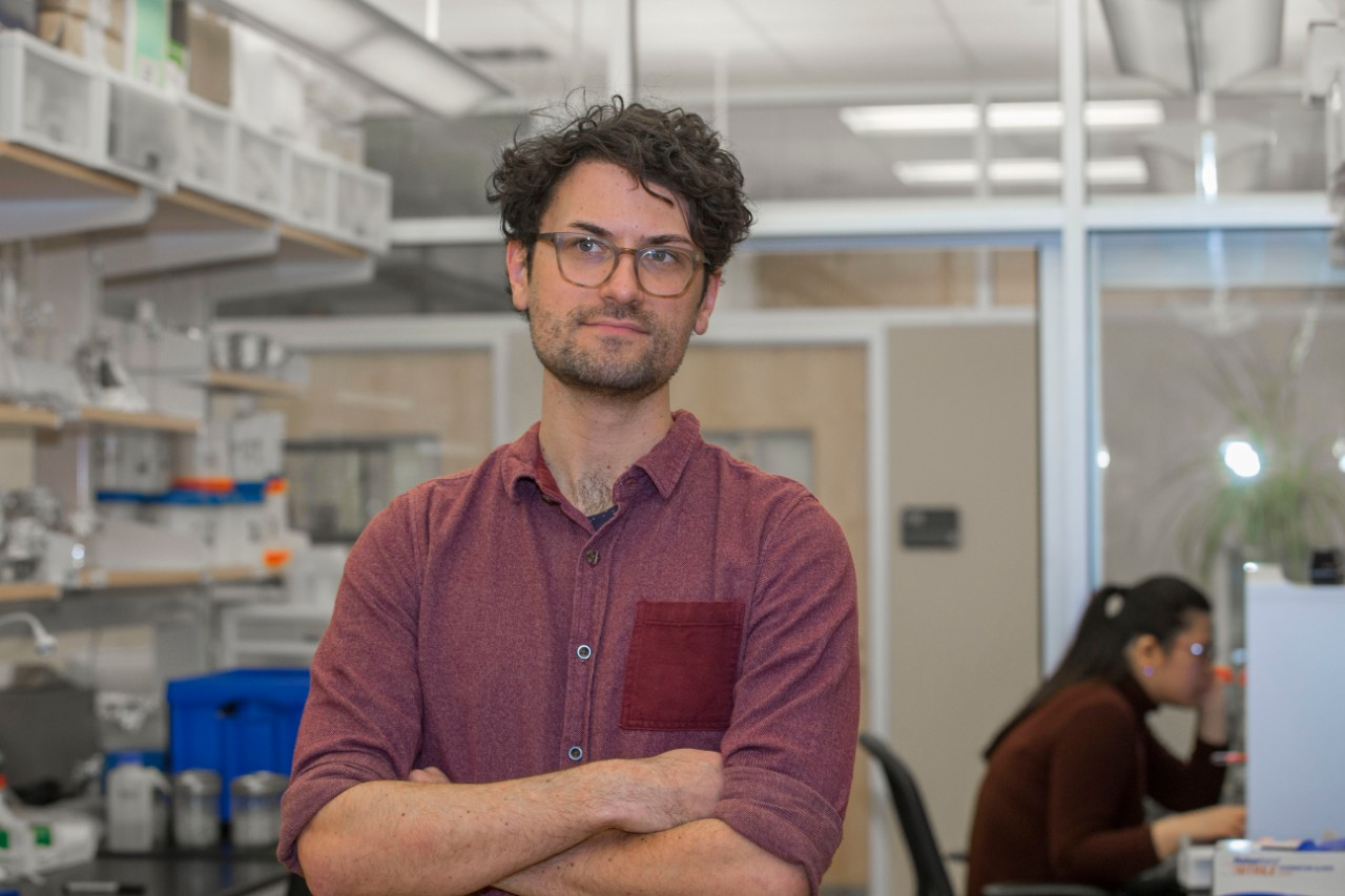UC student Geoffrey Finch stands with his arms crossed in a biology lab. Behind him are shelves of lab equipment and another student on a computer.