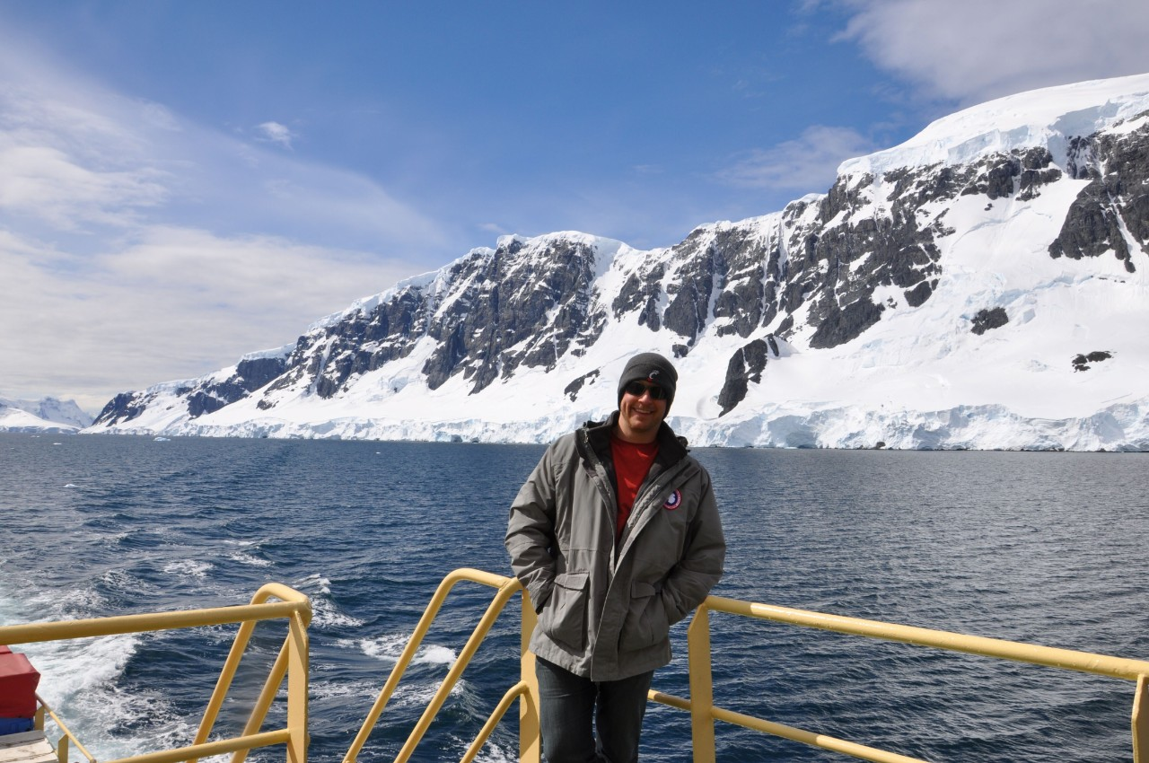 UC professor Joshua Benoit stands on the deck of a boat with Antarctic mountains behind him.