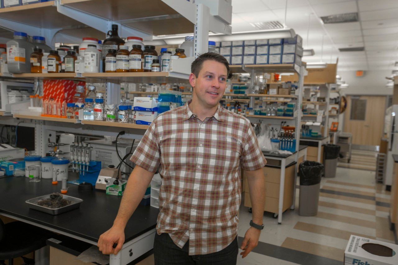 UC professor Joshua Benoit stands talking in his lab. Behind him are lab benches, microscopes, computers and shelves of lab equipment in a brightly lit room.