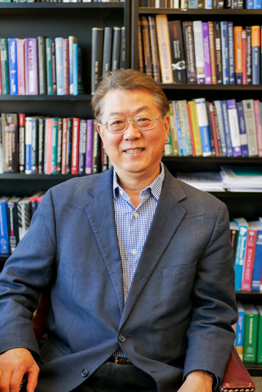 Ahn sits in front of books in office