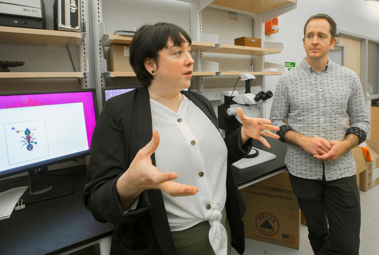 Alexis Dodson gestures while Nathan Morehouse looks on in a lab room full of microscopes and shelves full of equipment.