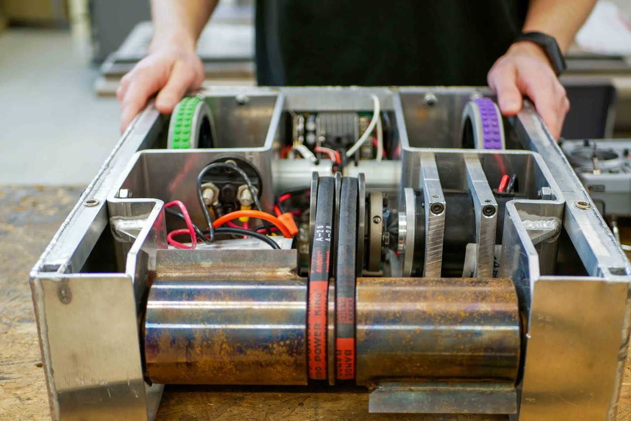 A closeup of  someone holding the innards of a battlebot showing the internal gears and wires.