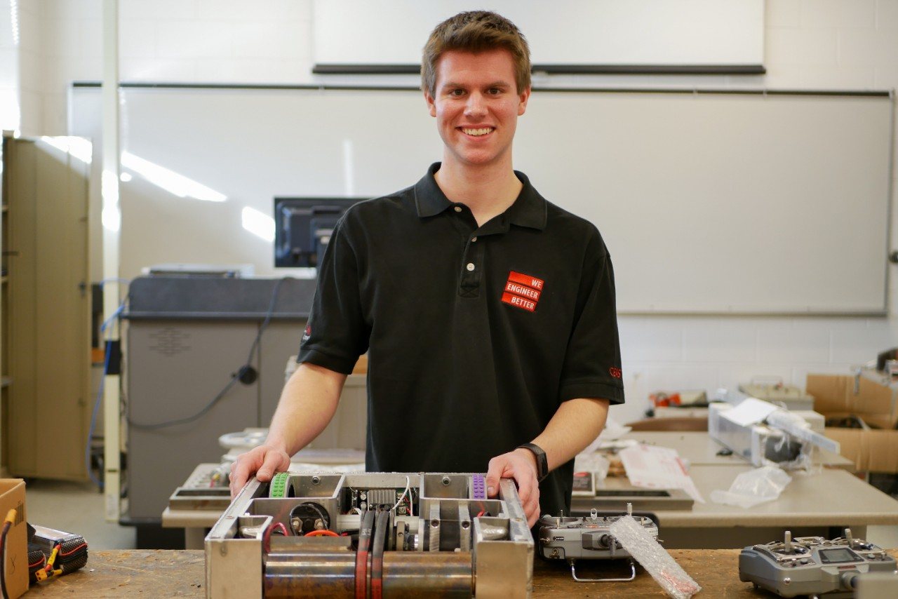 Woeste stands smiling in a lab with a BattleBot and remote controllers.