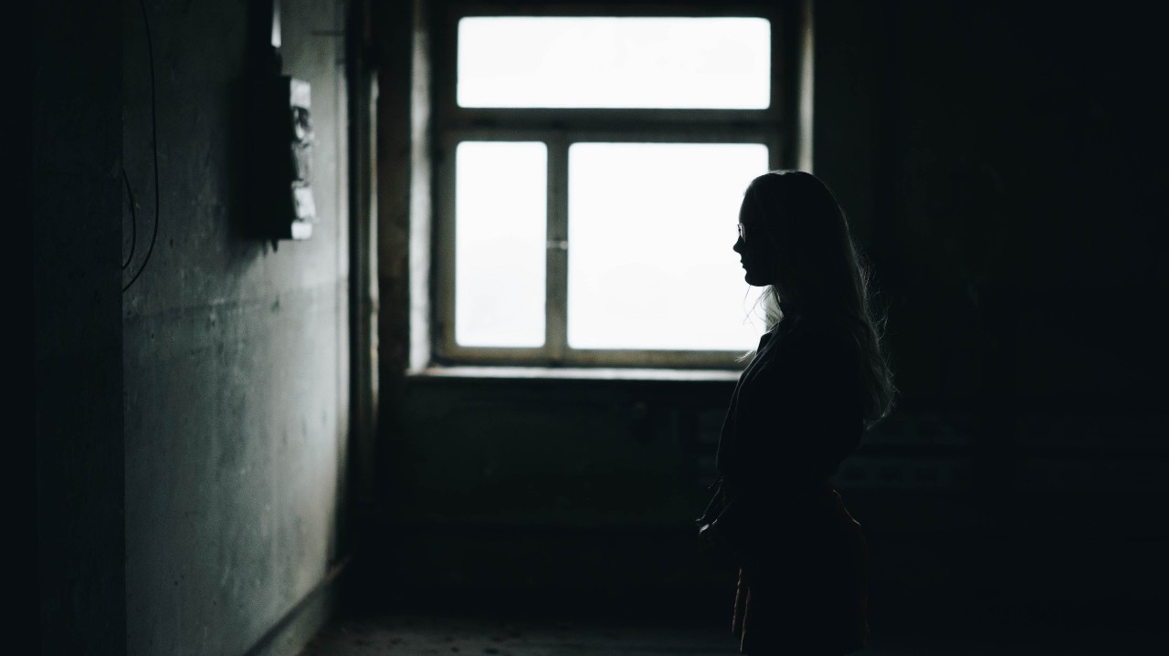A silhouette of a woman backlit by a window in a dark room