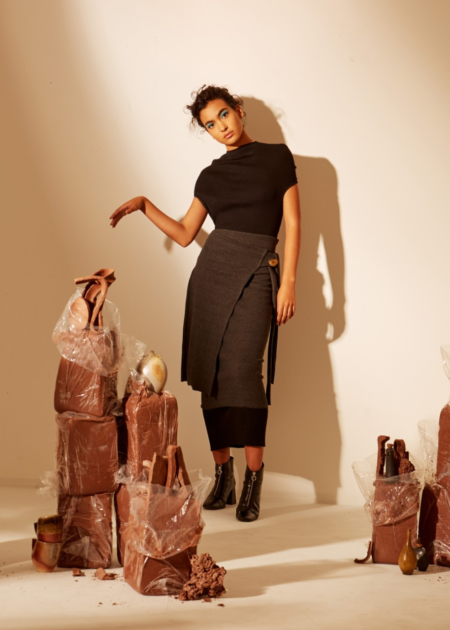Model poses in Tessa Clark's designs, among slabs of clay and ceramic art