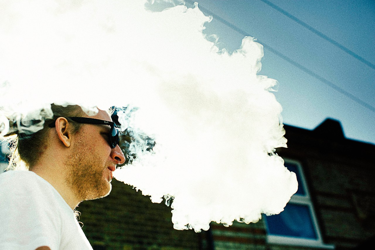 A young man exhales a thick cloud of vapor