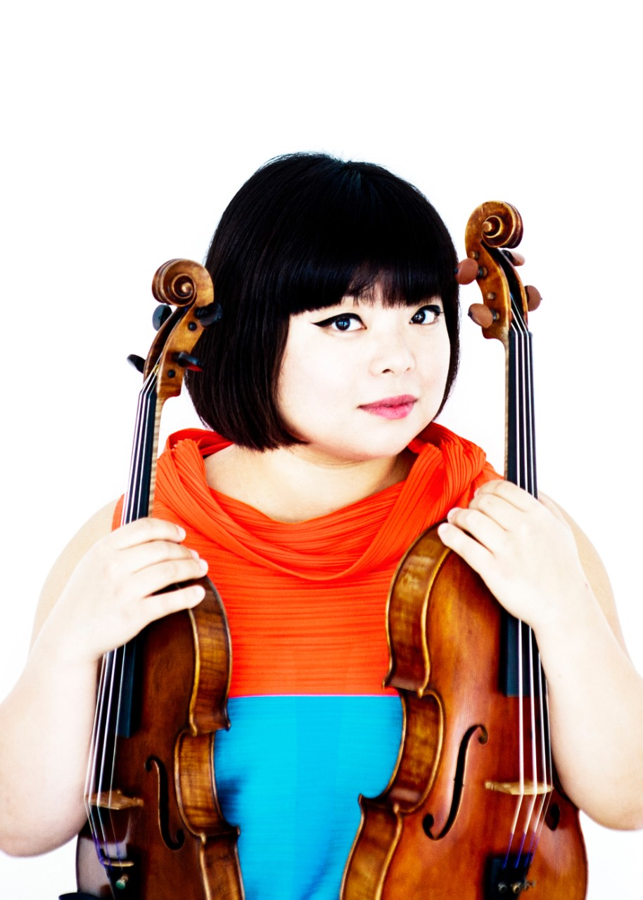 A photograph of CCM guest artist Yura Lee holding a violin and viola.