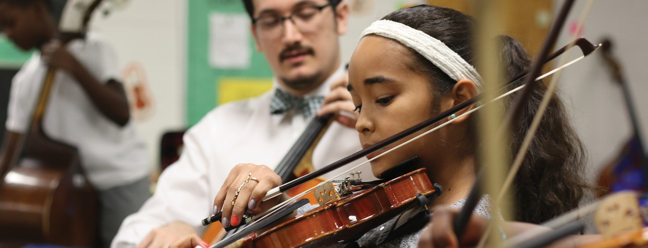 Young students learn how to play string instruments in a classroom.