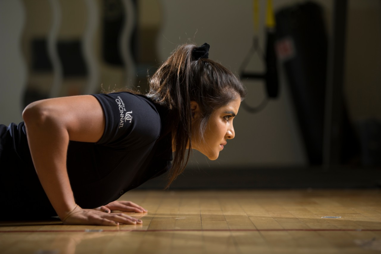 A sweaty UC student does push-ups in a gym.