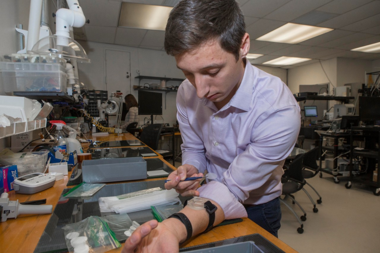 Andrew Jajack leans over his arm with his sleeve rolled up and a tiny  wristband sensor in a lab full of equipment in the background.