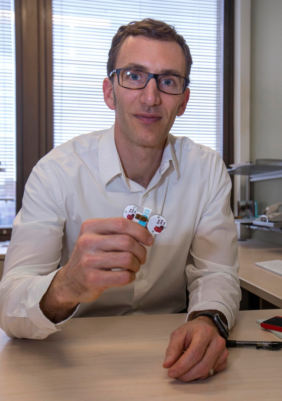 Jason Heikenfeld holds up one of his tiny sensors while sitting at his desk.