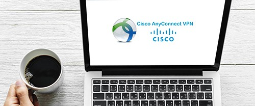 Open laptop computer with Cisco AnyConnect VPN logo next to a hand holding a cup of coffee.