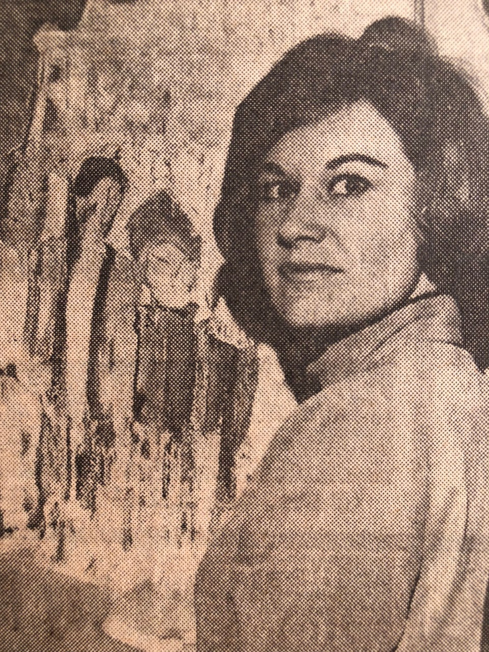 Black and white photo of woman with a 1960s hairstyle in front of a painting