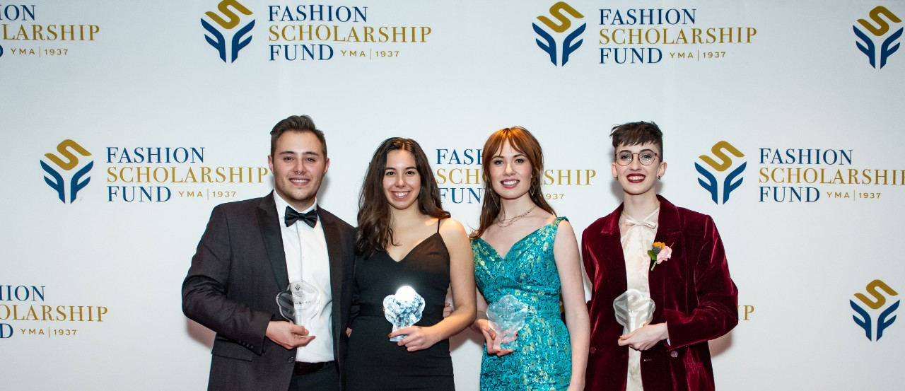 Four well-dressed students stand in front of a Fashion Scholarship Fund background.
